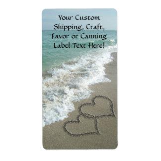 Dos corazones de la arena en la playa, océano romá etiqueta de envío