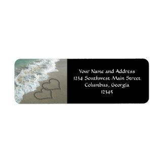 Dos corazones de la arena en la playa, océano romá etiquetas de remite