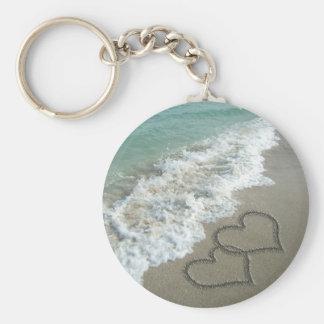 Dos corazones de la arena en la playa, océano romá llavero