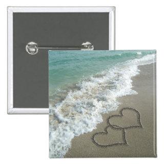 Dos corazones de la arena en la playa, océano romá pin cuadrada 5 cm