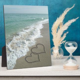 Dos corazones de la arena en la playa, océano romá placas para mostrar