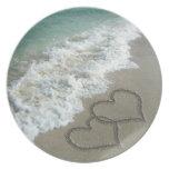 Dos corazones de la arena en la playa, océano romá plato para fiesta