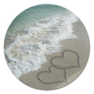 Dos corazones de la arena en la playa, océano romá plato