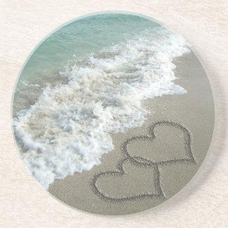 Dos corazones de la arena en la playa, océano romá posavaso para bebida
