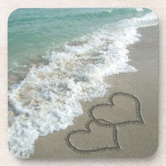 Dos corazones de la arena en la playa, océano romá posavasos de bebidas