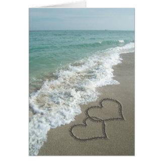 Dos corazones de la arena en la playa océano romá tarjeta