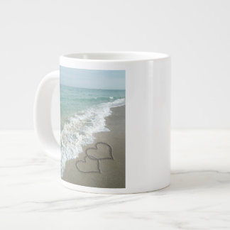 Dos corazones de la arena en la playa, océano romá taza grande