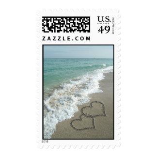Dos corazones de la arena en la playa, océano franqueo
