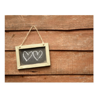 Dos corazones dibujados en la pequeña pizarra en j tarjeta postal