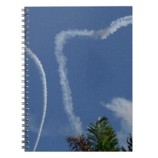 dos corazones dibujados por los aeroplanos sobre l libro de apuntes con espiral