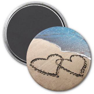 Dos corazones en la arena imán redondo 7 cm