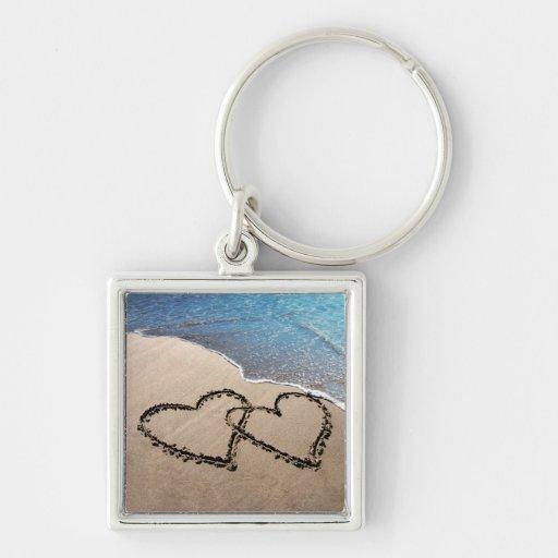 Dos corazones en la arena llaveros