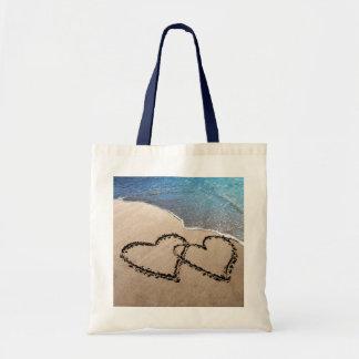 Dos corazones en la bolsa de asas de la arena