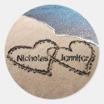 Dos corazones en la playa de la arena sellan a los etiquetas redondas