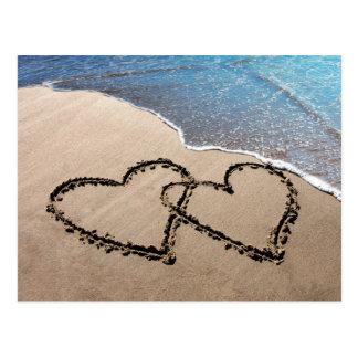 Dos corazones en la postal de la playa de la arena