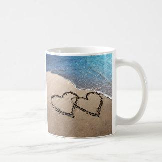 Dos corazones en la taza de la playa de la arena