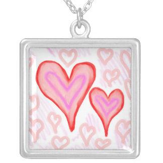 Dos corazones púrpuras rosados rojos rodeados por  pendiente personalizado