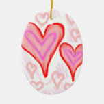 Dos corazones púrpuras rosados rojos rodeados por adorno ovalado de cerámica