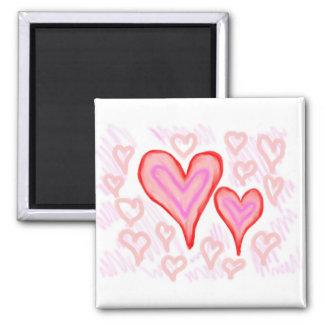Dos corazones púrpuras rosados rojos rodeados por  imán cuadrado
