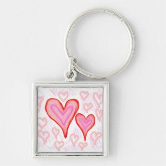 Dos corazones púrpuras rosados rojos rodeados por  llaveros personalizados