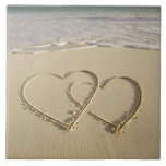 Dos corazones sobrepuestos dibujados en la playa c tejas  ceramicas