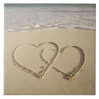 Dos corazones sobrepuestos dibujados en la playa c azulejo cuadrado grande