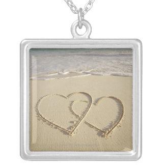 Dos corazones sobrepuestos dibujados en la playa c pendientes personalizados