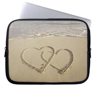 Dos corazones sobrepuestos dibujados en la playa c funda portátil