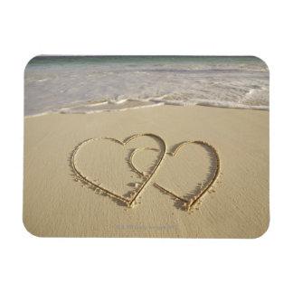 Dos corazones sobrepuestos dibujados en la playa c imán flexible