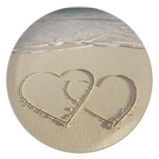 Dos corazones sobrepuestos dibujados en la playa c plato de comida