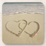 Dos corazones sobrepuestos dibujados en la playa c posavasos