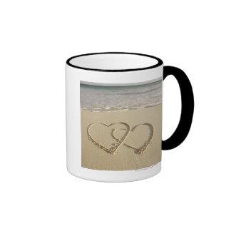 Dos corazones sobrepuestos dibujados en la playa c taza