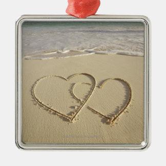Dos corazones sobrepuestos dibujados en la playa adorno cuadrado plateado