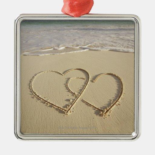 Dos corazones sobrepuestos dibujados en la playa ornamentos para reyes magos