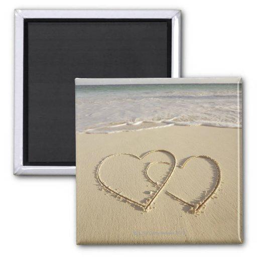 Dos corazones sobrepuestos dibujados en la playa imán para frigorifico