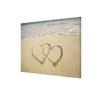 Dos corazones sobrepuestos dibujados en la playa lona envuelta para galerías