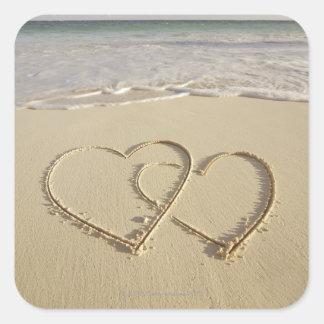 Dos corazones sobrepuestos dibujados en la playa pegatina cuadrada