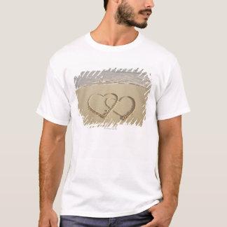 Dos corazones sobrepuestos dibujados en la playa playera