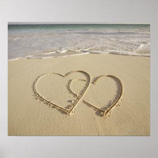Dos corazones sobrepuestos dibujados en la playa póster