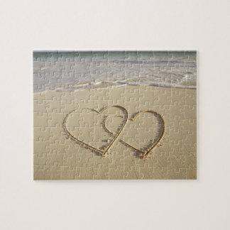 Dos corazones sobrepuestos dibujados en la playa puzzle con fotos