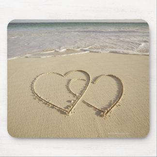 Dos corazones sobrepuestos dibujados en la playa tapetes de raton