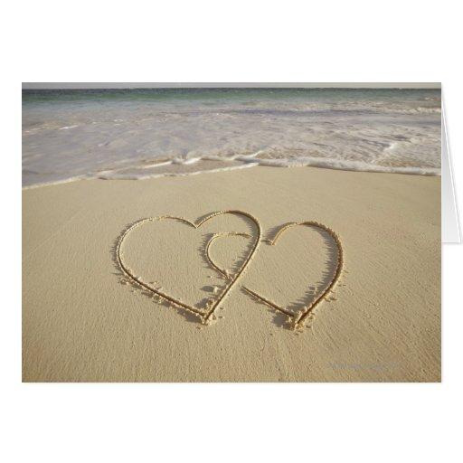 Dos corazones sobrepuestos dibujados en la playa tarjeta de felicitación
