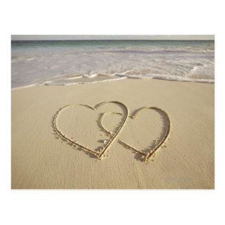 Dos corazones sobrepuestos dibujados en la playa postales