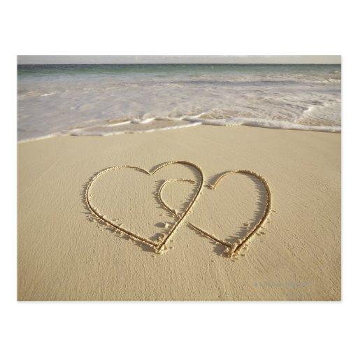 Dos corazones sobrepuestos dibujados en la playa tarjeta postal