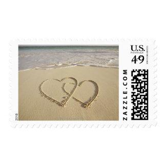 Dos corazones sobrepuestos dibujados en la playa timbres postales
