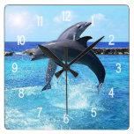 Dos delfínes que saltan haciendo trucos reloj cuadrado