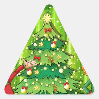 Dos duendes acercan al árbol de navidad pegatina triangular