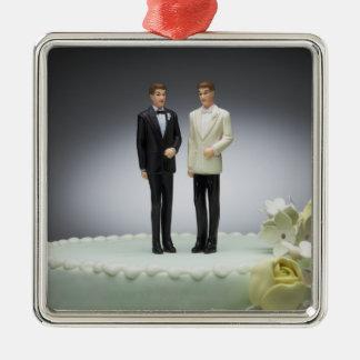 Dos estatuillas del novio encima del pastel de adorno navideño cuadrado de metal