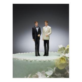 Dos estatuillas del novio encima del pastel de bod postales