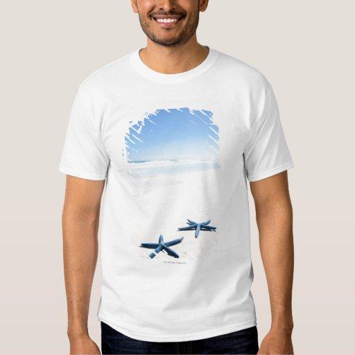 Dos estrellas de mar azules en el borde del agua camisas